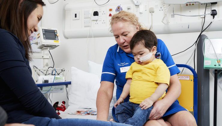 nurse with boy on bed in hospital